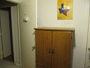 Armoire with NOTHING stacked on top under a Texas painting by my best friend in the UK